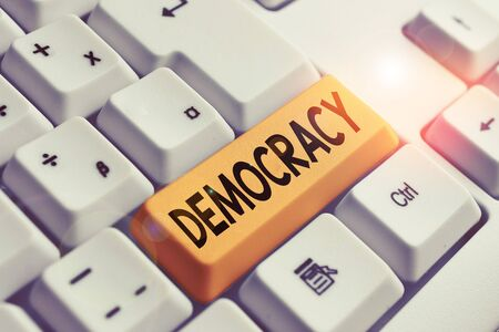 Handwriting text writing Democracy. Conceptual photo freedom of the showing to express their feelings and beliefs White pc keyboard with empty note paper above white background key copy space