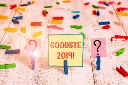 Handwriting text Goodbye 2019. Conceptual photo express good wishes when parting or at the end of last year Scribbled and crumbling sheet with paper clips placed on the wooden table Stockfoto
