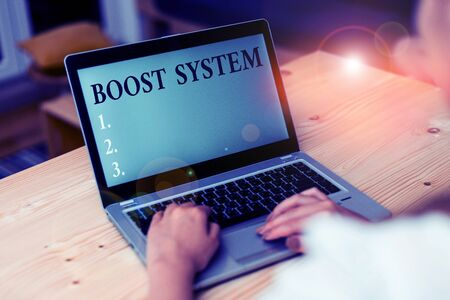 Word writing text Boost System. Business photo showcasing Rejuvenate Upgrade Strengthen Be Healthier Holistic approach woman laptop computer smartphone mug office supplies technological devices