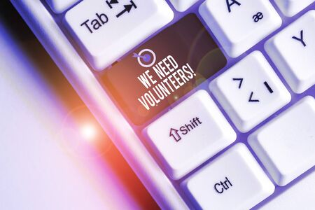 Text sign showing We Need Volunteers. Business photo showcasing someone who does work without being paid for it White pc keyboard with empty note paper above white background key copy space