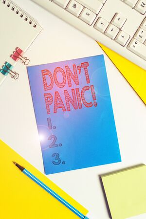 Conceptual hand writing showing Don T Panic. Concept meaning suddenly feel so worried or frightened that you can not behave Colored paper binder clip sheets white desk empty space Imagens