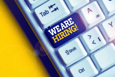 Conceptual hand writing showing We Are Hiring. Concept meaning recently you employ someone or pay someone to do particular job White pc keyboard with note paper above the white background