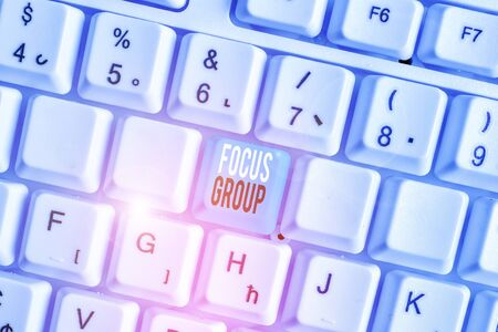 Writing note showing Focus Group. Business concept for showing assembled to participate in discussion about something White pc keyboard with note paper above the white background Banco de Imagens