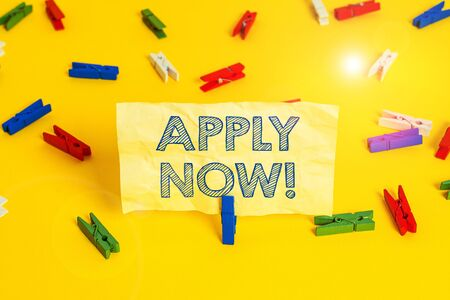 Writing note showing Apply Now. Business concept for request something officially in writing or by sending in form Colored clothespin papers empty reminder yellow floor background office