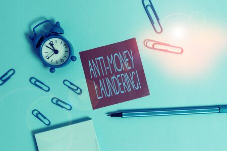 Conceptual hand writing showing Anti Money Laundering. Concept meaning regulations stop generating income through illegal actions Alarm clock notepad sticky note marker colored background