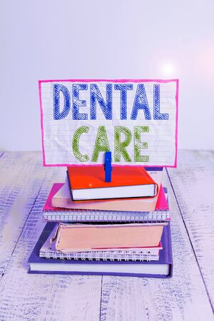 Word writing text Dental Care. Business photo showcasing maintenance of healthy teeth or to keep it clean for future pile stacked books notebook pin clothespin colored reminder white wooden