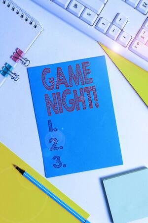 Conceptual hand writing showing Game Night. Concept meaning usually its called on adult play dates like poker with friends Colored paper binder clip sheets white desk empty space