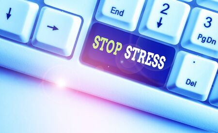 Conceptual hand writing showing Stop Stress. Concept meaning Seek help Take medicines Spend time with loveones Get more sleep White pc keyboard with note paper above the white background