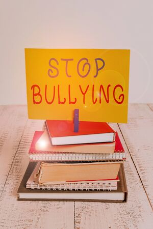 Conceptual hand writing showing Stop Bullying. Concept meaning Fight and Eliminate this Aggressive Unacceptable Behavior pile stacked books notebook pin color reminder white wooden