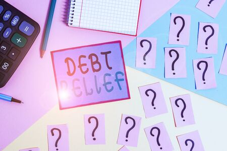 Handwriting text Debt Relief. Conceptual photo partial or total remission of it especially those by countries Mathematics stuff and writing equipment above pastel colours background 写真素材