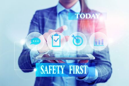 Word writing text Safety First. Business photo showcasing Avoid any unnecessary risk Live Safely Be Careful Pay attention Female human wear formal work suit presenting presentation use smart device