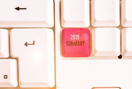 Conceptual hand writing showing 2019 Summary. Concept meaning brief comprehensive especially covering the main points of 2019 White pc keyboard with note paper above the white background