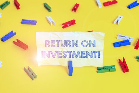 Writing note showing Return On Investment. Business concept for perforanalysisce measure used evaluate efficiency of investment Colored clothespin papers empty reminder yellow floor background office
