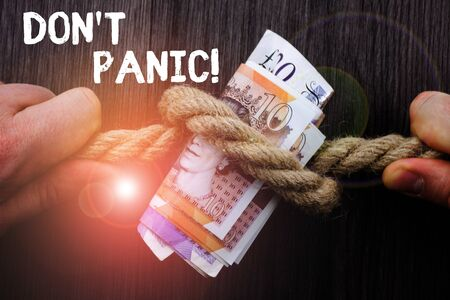 Writing note showing Don T Panic. Business concept for suddenly feel so worried or frightened that you can not behave Front view wooden background two hands knot rope bills inside symbol