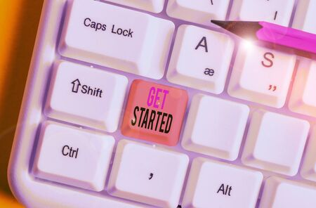 Conceptual hand writing showing Get Started. Concept meaning asking someone to begin task endeavour or process right now White pc keyboard with note paper above the white background Фото со стока
