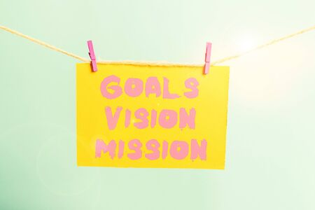 Conceptual hand writing showing Goals Vision Mission. Concept meaning practical planning process used to help community group Clothespin rectangle shaped paper reminder white wood desk