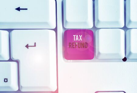 Conceptual hand writing showing Tax Refund. Concept meaning refund on tax when the tax liability is less than the tax paid White pc keyboard with note paper above the white background