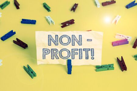 Writing note showing NonProfit. Business concept for not making or conducted primarily to make profit organization Colored clothespin papers empty reminder yellow floor background office