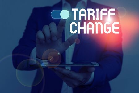 Word writing text Tariff Change. Business photo showcasing Amendment of Import Export taxes for goods and services Male human wear formal work suit presenting presentation using smart device