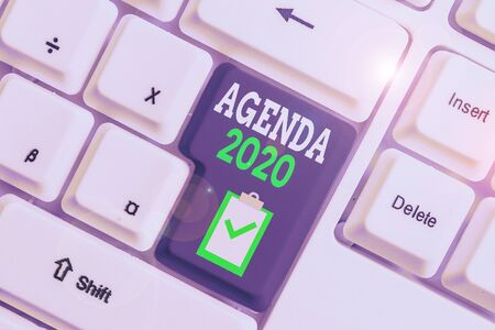 Handwriting text writing Agenda 2020. Conceptual photo list of activities in order which they are to be taken up White pc keyboard with empty note paper above white background key copy space Stock Photo
