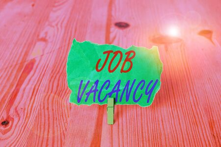 Text sign showing Job Vacancy. Business photo showcasing empty or available paid place in small or big company Empty reminder wooden floor background green clothespin groove slot office Stok Fotoğraf