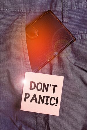 Conceptual hand writing showing Don T Panic. Concept meaning suddenly feel so worried or frightened that you can not behave Small wallet inside trouser front pocket near notation paper 스톡 콘텐츠