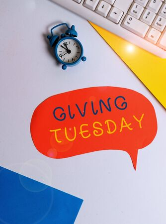Handwriting text writing Giving Tuesday. Conceptual photo international day of charitable giving Hashtag activism Flat lay with copy space on bubble paper clock and paper clips 写真素材