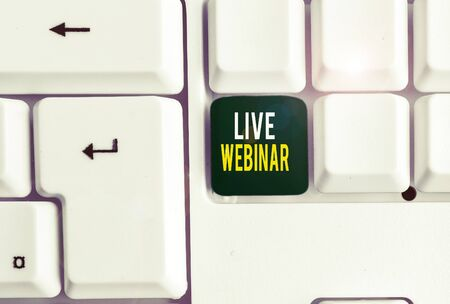 Conceptual hand writing showing Live Webinar. Concept meaning Interactive seminar transmitted over the web Real Time White pc keyboard with note paper above the white background