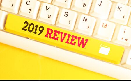 Text sign showing 2019 Review. Business photo text New trends and prospects in tourism or services for 2019 White pc keyboard with empty note paper above white background key copy space
