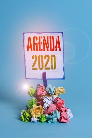 Word writing text Agenda 2020. Business photo showcasing list of activities in order which they are to be taken up Reminder pile colored crumpled paper clothespin reminder blue background