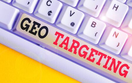 Text sign showing Geo Targeting. Business photo text Digital Ads Views IP Address Adwords Campaigns Location White pc keyboard with empty note paper above white background key copy space Фото со стока