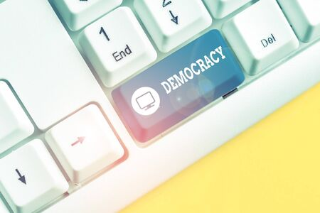 Text sign showing Democracy. Business photo showcasing freedom of the showing to express their feelings and beliefs White pc keyboard with empty note paper above white background key copy space Фото со стока