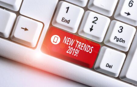 Text sign showing New Trends 2019. Business photo text general direction in which something is developing White pc keyboard with empty note paper above white background key copy space Фото со стока