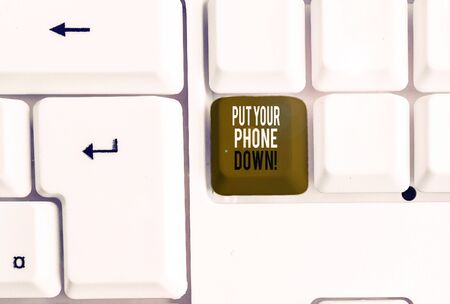 Text sign showing Put Your Phone Down. Business photo showcasing end telephone connection saying goodbye caller White pc keyboard with empty note paper above white background key copy space Фото со стока