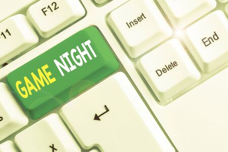 Word writing text Game Night. Business photo showcasing event in which folks get together for the purpose of getting laid White pc keyboard with empty note paper above white background key copy space Banco de Imagens