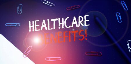 Writing note showing Healthcare Benefits. Business concept for monthly fair market valueprovided to Employee dependents Scissors and writing equipments plus math book above textured backdrop