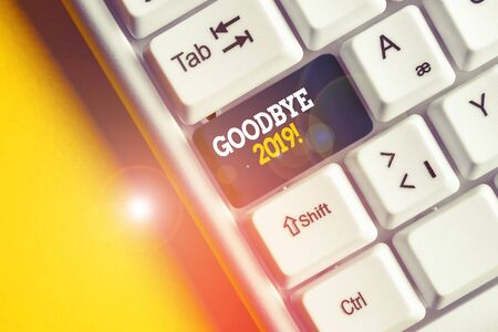 Conceptual hand writing showing Goodbye 2019. Concept meaning express good wishes when parting or at the end of last year White pc keyboard with note paper above the white background
