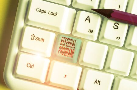 Conceptual hand writing showing Referral Program. Concept meaning internal recruitment method employed by organizations White pc keyboard with note paper above the white background Stock Photo