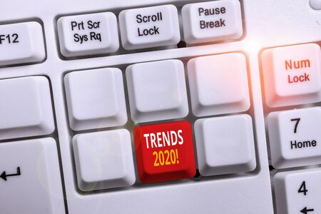 Conceptual hand writing showing Trends 2020. Concept meaning general direction in which something is developing or changing White pc keyboard with note paper above the white background