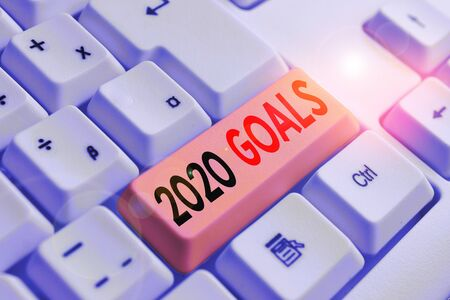 Handwriting text writing 2020 Goals. Conceptual photo A plan to do for something new and better for the coming year White pc keyboard with empty note paper above white background key copy space Stock Photo