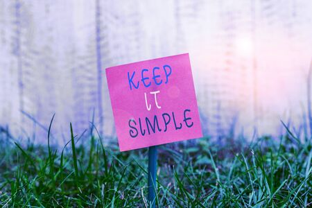 Writing note showing Keep It Simple. Business concept for to make something easy to understand and not in fancy way Plain paper attached to stick and placed in the grassy land