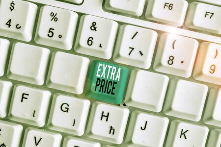 Writing note showing Extra Price. Business concept for extra price definition beyond the ordinary large degree White pc keyboard with note paper above the white background Stockfoto