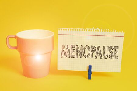 Writing note showing Menopause. Business concept for Period of peranalysisent cessation or end of menstruation cycle Cup empty paper blue clothespin rectangle shaped reminder yellow office