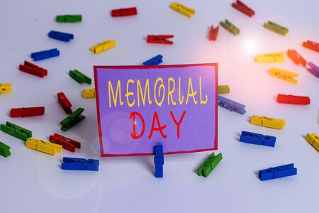 Conceptual hand writing showing Memorial Day. Concept meaning To honor and remembering those who died in military service Colored clothespin papers empty reminder white floor office