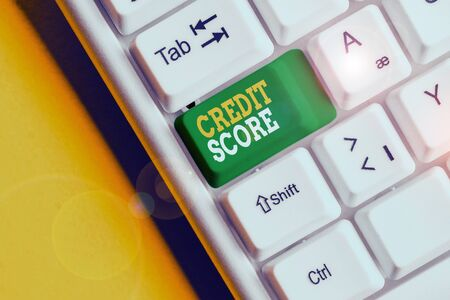 Conceptual hand writing showing Credit Score. Concept meaning Represent the creditworthiness of an individual Lenders rating White pc keyboard with note paper above the white background Banco de Imagens