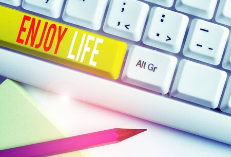 Handwriting text writing Enjoy Life. Conceptual photo Any thing, place,food or demonstrating, that makes you relax and happy White pc keyboard with empty note paper above white background key copy space