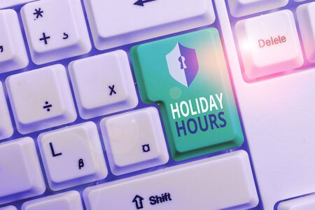Handwriting text writing Holiday Hours. Conceptual photo employee receives twice their normal pay for all hours White pc keyboard with empty note paper above white background key copy space