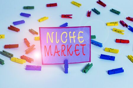 Conceptual hand writing showing Niche Market. Concept meaning Subset of the market on which specific product is focused Colored clothespin papers empty reminder white floor office