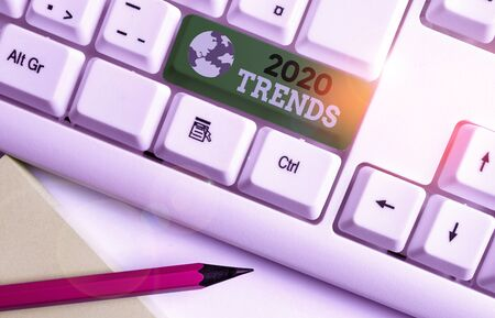 Writing note showing 2020 Trends. Business concept for things that is famous for short period of time in current year White pc keyboard with note paper above the white background
