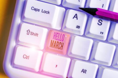 Conceptual hand writing showing Hello March. Concept meaning musical composition usually in duple or quadruple with beat White pc keyboard with note paper above the white background Imagens